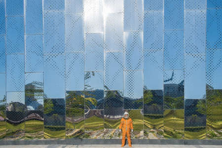 Astronaut wearing orange spacesuit and space helmet near a spaceport with huge mirror wall with reflection of blue sky outdoors.