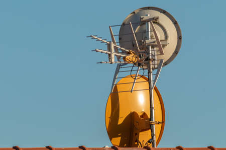 television antennas on the roof of a house outdoors