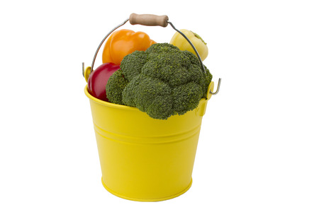 assort: Vegetables assort in the yellow bucket isolated on the white background Stock Photo