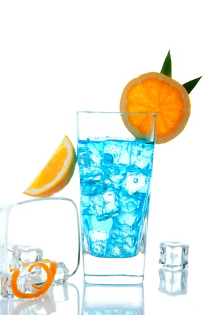 Blue Lagoon cocktail decorated with orange and pineapple, filled with ice on a white background photo