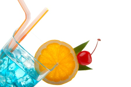 Blue hawaiian curacao cold cocktail decorated with orange,  pineappleand and cherry, filled with ice isolated on a white background photo
