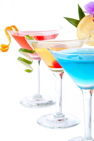 Summer Tropical Martini Cocktails with vodka, apple and peach liqueur, pineapple and cranberry juice, lime, lemon, blue curacao, maraschino cherry, and orchid isolated on a white background photo