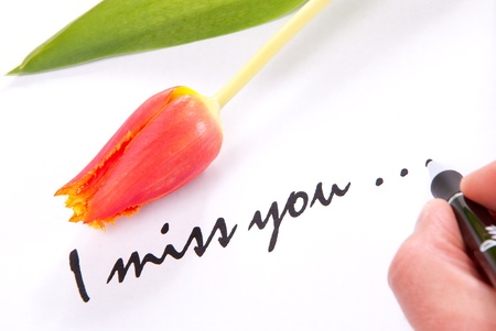 heartache: Hand writing I miss you to his lovely sweetheart on a piece of papper decorated with the red spring tulip flower Stock Photo