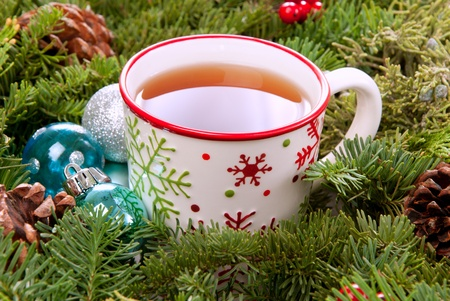 Christmas mug with tea decorated  with red and green snowflakes pine and fir cone ornamentin the morning photo