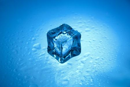 melting: Cubo de hielo congelado uno con gotas de agua clara aislado en un fondo azul