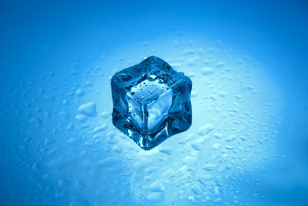 defrost: One frozen ice cube with clear water drops isolated on a blue background