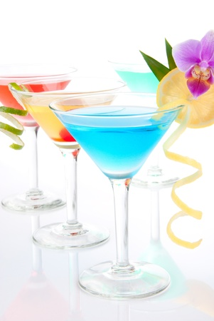 Three Summer Tropical Martini and One Margarita Cocktails with vodka, apple and peach liqueur, pineapple and cranberry juice, lime, lemon, blue curacao, maraschino cherry, and orchid isolated on a white background photo