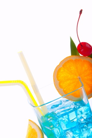 Blue Lagoon cocktail with malibu rum, blue curacao, vodka, tequila, lime juice, two straws decorated with red maraschino cherry, pineapple leaf and orange wheel isolated on a white background photo