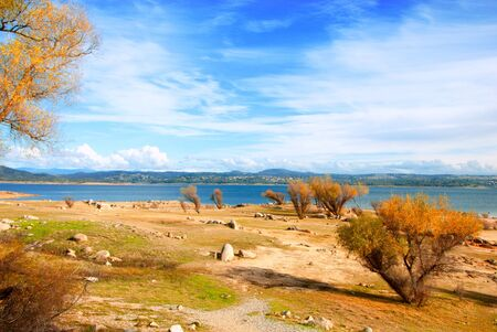 Folsom Lake is a reservoir in Northern California near El Dorado and Sacramento, constructed in 1955 to control the American River. Photo made at a day time on perfect blue sky background with clouds photo