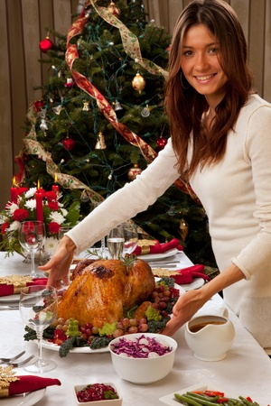 Garnished roasted turkey in young beautiful woman hands prepared for traditional family dinner decorated with salad, fruits, vegetables, vine and shampagne glasses on Christmas tree background Stock Photo