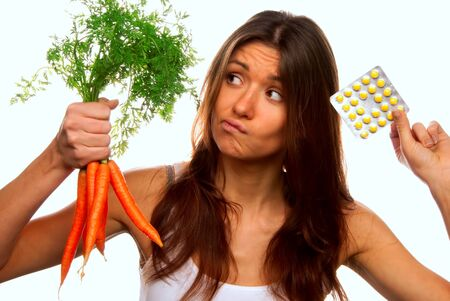 thinks: Young beautiful woman thinks deeply and making decision between organic fresh carrots and medical tablets to make the right choice and have no doubts. Most popular image series