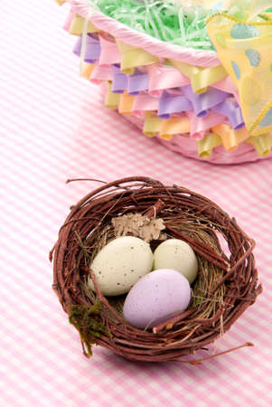 Easter Painted Colorful eggs in birds nest  for sunday morning on a pastel color background photo