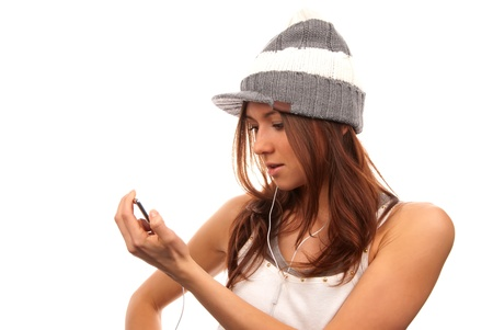 Pretty young female looking and reading text message on her new modern cell phone mobile and listening music in headphones isolated on a white background photo
