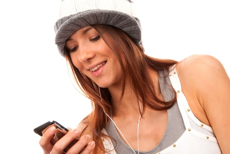 Pretty young teenage girl typing and reading text message on her new modern cell phone mobile and listening music in headphones isolated on a white background photo
