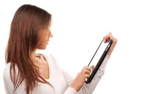 Pretty brunette woman typing on her new electronic tablet touch pad computer pc one finger touches the digital screen isolated on a white background