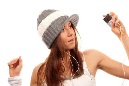 Pretty female in headphones listening music and  looking  her new modern mp3 player isolated on a white background photo