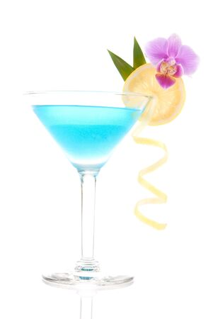 Blue lagood cocktail with vodka, triple sec, white cranberry juice, lime, lemon wheel, pineapple leaf and orchid in martini glass isolated on a white background Фото со стока