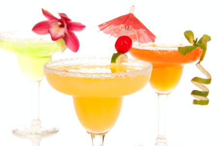 Margaritas cocktails composition decorated with lime, orchid, cherry and cocktail umbrella isolated on a white background photo