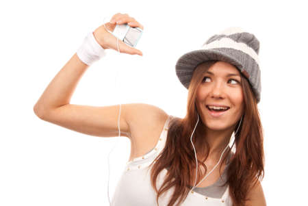 Pretty young woman listening dance music in earphones or headphoneson mp3 player mobile isolated on a white background photo