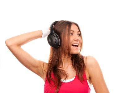 Luisteren muziek meisje in hoofd telefoons zingen, glimlachend en houden haar hand naar zwarte hoofd telefoon in roze top geïsoleerd op een witte achtergrond Stockfoto