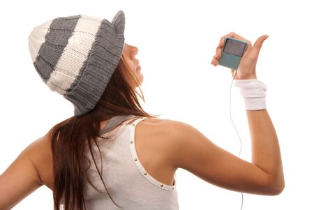 Girl listening to music on mp3 player in white headphones wearing hip-hop style hat and dance top isolated on white background photo