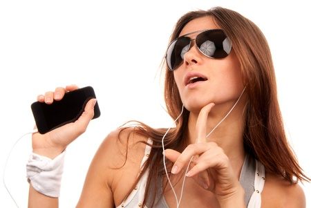 Young fashion woman in sunglasses enjoy listening to music in white earphones isolated on a white background Stock Photo - 8652423
