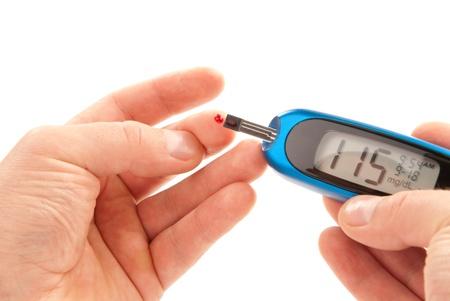 diabetes: Paciente diab�tico haciendo uso de ultra gluc�metro mini y peque�a gota de sangre de tiras de prueba y dedo aislado en un fondo blanco en la prueba de glucosa nivel sangre. Dispositivo muestra 115 mgdL, que es normal