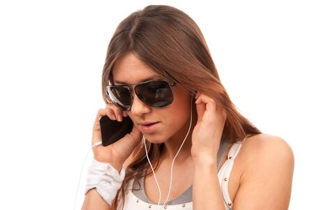 Young brunette fashion spy woman in sunglasses enjoy listening to music in white earphones and talking on new mobile cellphone isolated on a white background photo