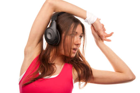 Pretty fitness brunette woman listening enjoying music in headphones, smiling and laughing isolated on a white background Stock Photo - 8703493