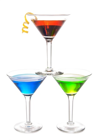 Colorful Martini Cocktails drink blue green and red on top composition with vodka, light rum, gin, tequila, blue curacao, lime juice in classic cocktail glasses isolated on a white background photo