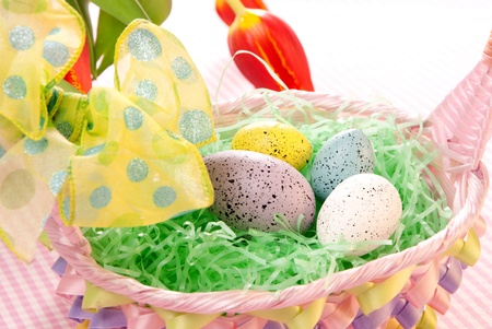 Easter blue, pink, yellow Painted Colorful eggs in basket with spring tulips on a pastel background photo