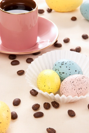Easter eggs Sunday morning  pink, blue and yellow eggs, cup of espresso coffee and beans for happy Christian family on a pastel color background photo