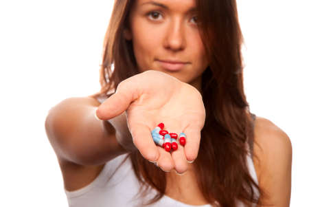 Brunette female doctor offering pills capsules red and blue to the patient in hand and looking at camera isolated on a white background. Focus on tablets photo