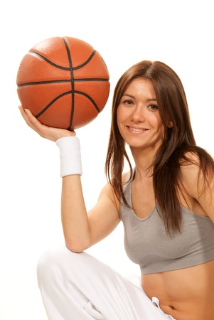 Pretty brunette woman holding Basketball in hand and smiling isolated on a white background photo