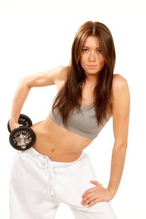 Pretty Fitness woman with athletic body lifting weights dumbbells isolated on a white background photo