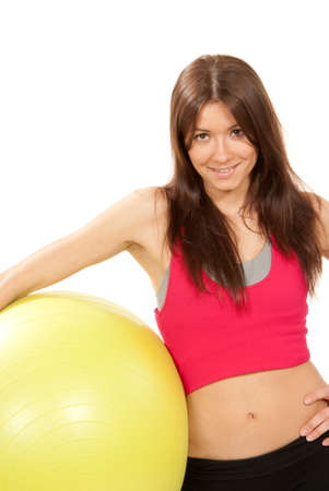 ball stretching: Pretty slim female fitness instructor holds pilates ball in gym with athletic muscle body on a white background
