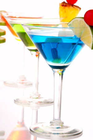 Tropical Martini Cocktails drink blue green and red on top composition with vodka, light rum, gin, tequila, blue curacao, lime juice in classic cocktail glasses isolated on a white background photo