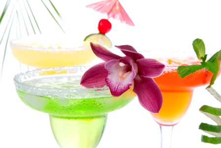 Three Margaritas cocktails composition decorated with lime, orchid, cherry, apple, peach and drink umbrella in margarita glasses  isolated on a white background photo