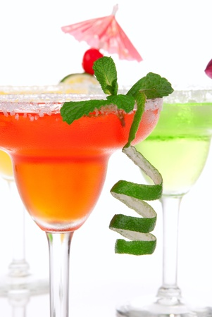 Strawberry, lime, apple Margaritas cocktails composition decorated with twisted lime, mint, cherry, cocktail umbrella in margarita glass isolated on a white background photo