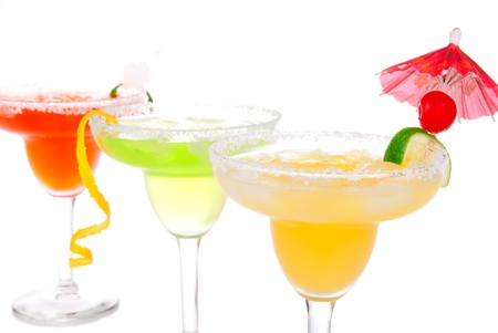 daiquiri alcohol: Strawberry, lime, apple Margaritas cocktails composition decorated with twisted orange,  lime, mint, cherry, cocktail umbrella in margarita glass isolated on a white background Stock Photo