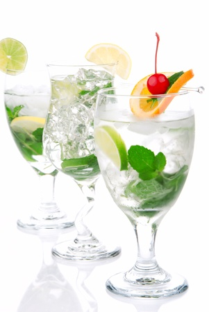 Classic Citrus Mojito cocktails with light rum, vodka, gin, lime, spring of mint, simple soda, orange, maraschino cherry and syrup in cocktail glasses isolated on a white background