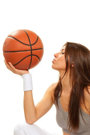 Pretty sexy young Basketball brunette cheerleader woman player kissing and lovely holding basket ball in hand wearing top isolated on a white background photo