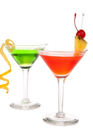 Green and Red cocktails composition with vodka, light rum, gin, tequila, blue curacao, lime juice, lemonade, lemon slice, maraschino cherry in martini cocktail grass isolated on a white background