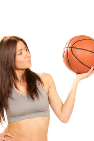 Pretty brunette cheerleader woman holding Basketball ball in hand and smiling isolated on a white background photo