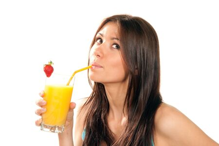 Beautiful Healthy lifestyle brunette woman drinking orange juice cocktail with strawberry with drinking straw in highball glass and looking up isolated on a white background Stock Photo