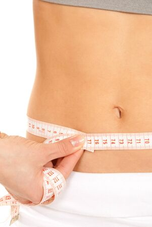 Athletic fit slim female measuring her waist metric tape measure after a fitness diet  isolated over white background photo