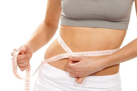 waist: Atl�tica femenino delgada forma medir su medida de cinta m�trica de cintura despu�s de una dieta aislada sobre fondo blanco