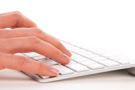 keyboard: Woman hands typing on the remote wireless computer keyboard in an office at a workplace isolated on a white background