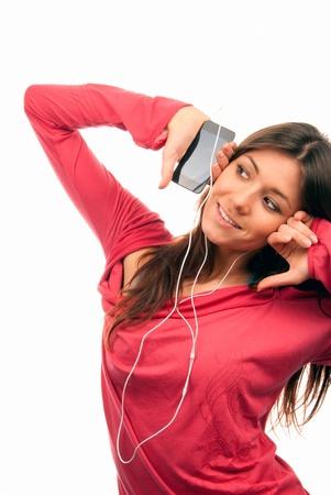 Pretty young woman listening music on her new cellular touch mp3 player in headphones wearing dance pink top, isolated on white background photo