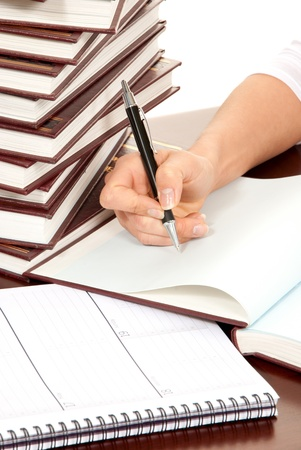 Writer business person hand with pen signing document. On the table stack of books organizer notebook Stock Photo - 8921982